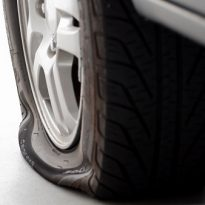 A flat tire is the focus isolated on white